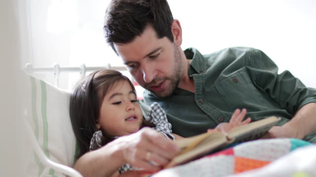 father reading daughter a bedtime story - bedtime stock videos & royalty-free footage