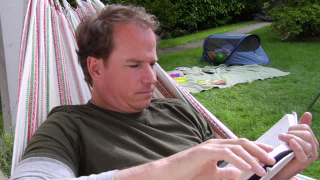 ms father reading in hammock as baby plays in tent in background/ vancouver, bc  - see other clips from this shoot 1101 stock videos & royalty-free footage