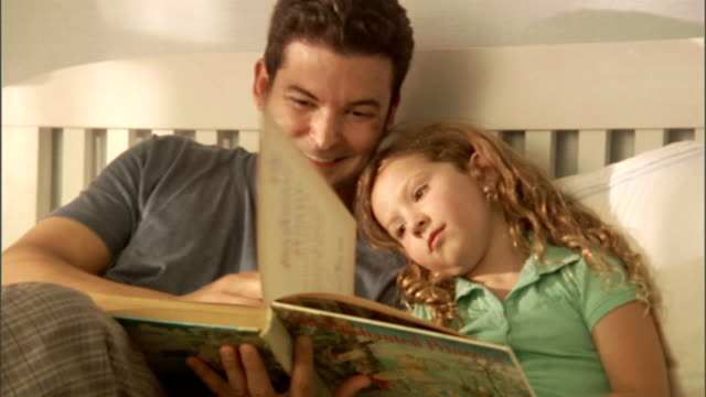vídeos y material grabado en eventos de stock de cu, father reading to daughter (4-5) on bed - recostarse