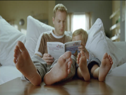 father reads out a book to his young son sit as they sit side by side on the sofa - side by side stock videos & royalty-free footage