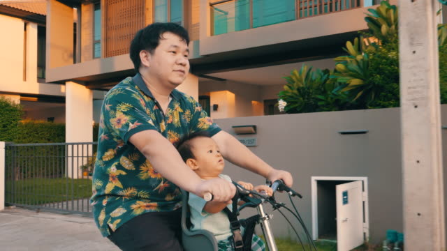father riding his bike in the sunny park with his son in the front seat - bicycle seat stock videos & royalty-free footage