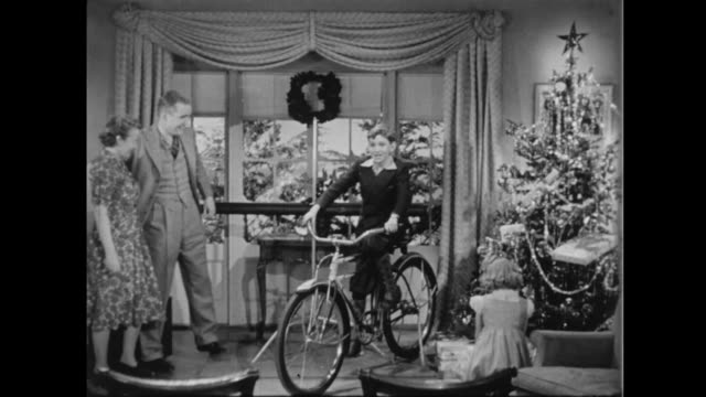 vídeos de stock, filmes e b-roll de 1957 father rolls up projection screen to reveal bicycle as children realize christmas gifts have arrived - 1957