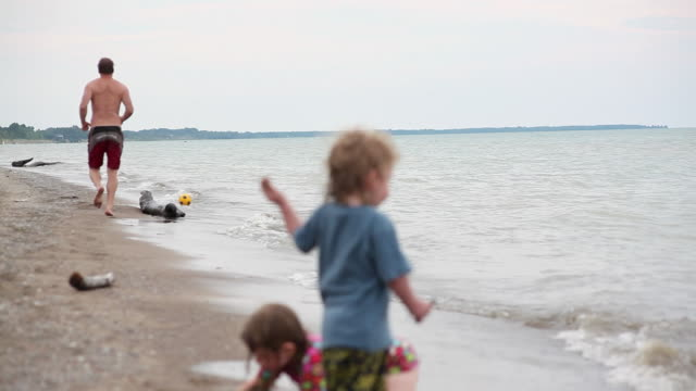 ws father runing to catching ball on beach as little girl and boy playing in sand / toronto, ontario, canada - kelly mason videos stock-videos und b-roll-filmmaterial
