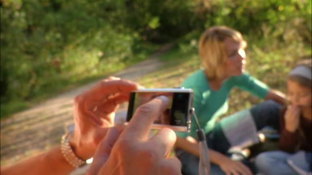 vídeos y material grabado en eventos de stock de father selecting features on digital camera lcd screen and taking photograph of family picnic - cesta de picnic