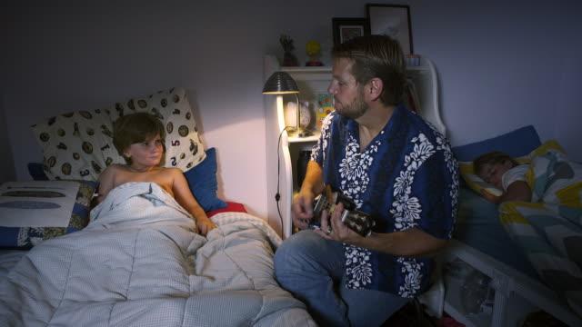 vidéos et rushes de father serenades his son to bed - close to wide - lampe électrique