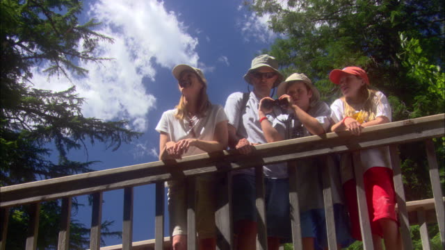 vidéos et rushes de a father shares his excitement with his family as they stand at a railing in glacier national park. - casquette de baseball