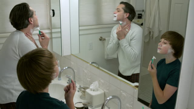 Father shaving himself and his son imitating him