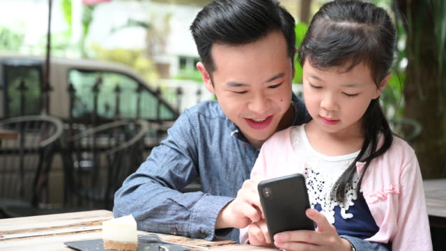 father showing daughter smartphone and talking - digital native stock videos & royalty-free footage
