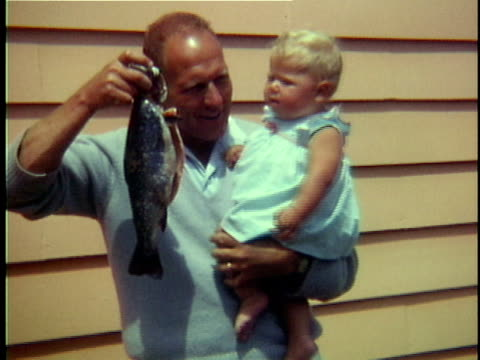 1965 ms father showing dead fish to baby girl, middlebury, vermont, usa - genderblend stock videos & royalty-free footage