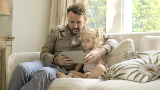 father showing digital tablet to his daughter on sofa. - gemütlich stock-videos und b-roll-filmmaterial