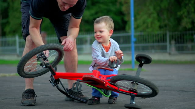 father showing son how to repair bicycle - stabilisers stock videos & royalty-free footage