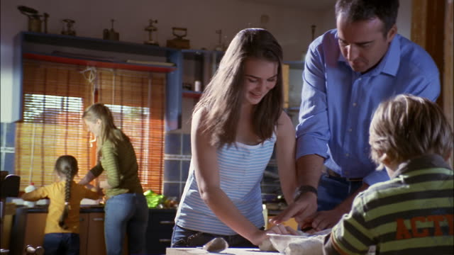 A father shows his teenage daughter how to knead dough.