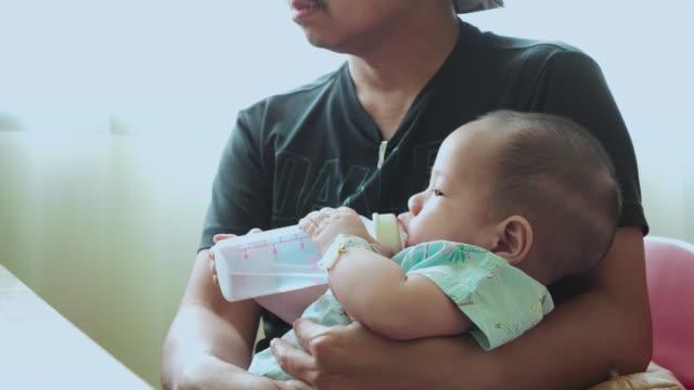 父は赤ちゃんの息子にボトルを与えながら座ります。 - 粉ミルク点の映像素材/bロール
