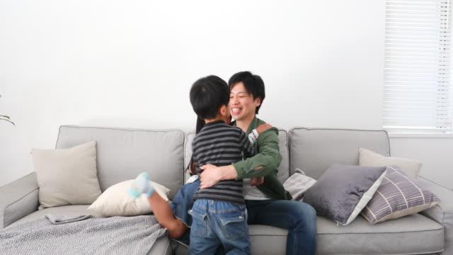 2人の子供を抱きしめて座っている父 - 到着点の映像素材/bロール