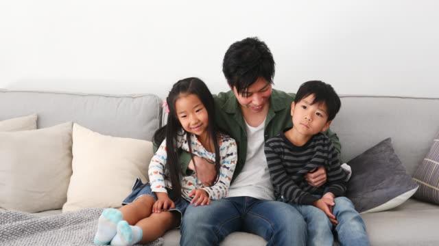 2人の子供を抱きしめて座っている父 - 兄弟点の映像素材/bロール