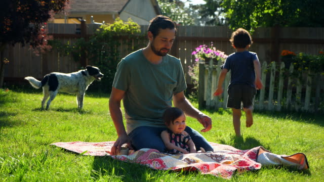 MS Father sitting on blanket in backyard with infant daughter on summer morning