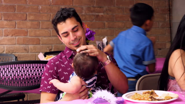 MS Father sitting with smiling infant on lap during birthday party