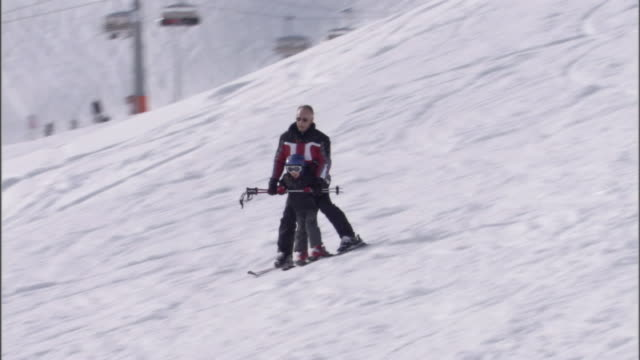 a father skis down the hill with his young son. - ski resort stock videos & royalty-free footage