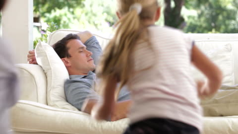father sleeping on sofa gets woken by two noisy children - tickling stock videos & royalty-free footage