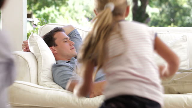 Father Sleeping On Sofa Gets Woken By Two Noisy Children