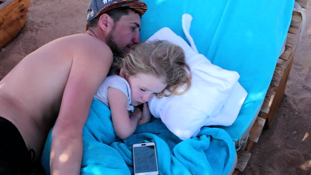 father sleeps with his daughter on a sun lounger. egypt. sharm el-sheikh. - towel stock videos & royalty-free footage