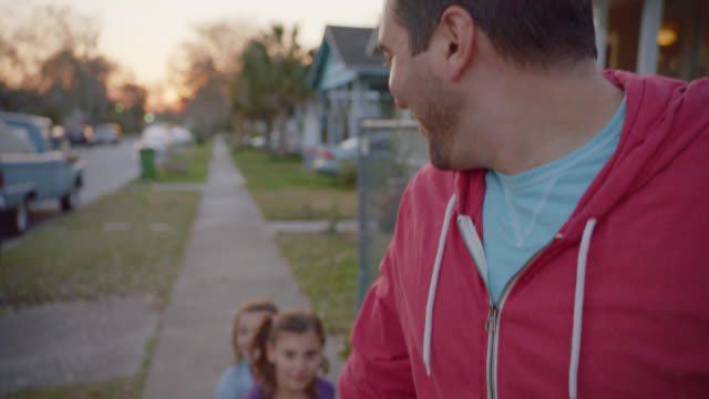 MS SLO MO. Father smiles and turns to look at daughters pulled behind in little red wagon.