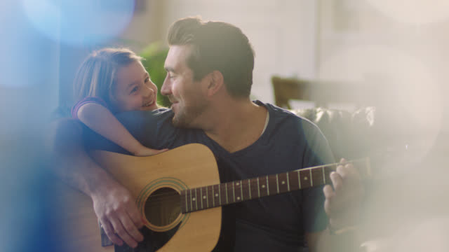 vídeos de stock, filmes e b-roll de ms. father smiles at daughter leaning on his shoulder as he sits and plays acoustic guitar. - vida simples