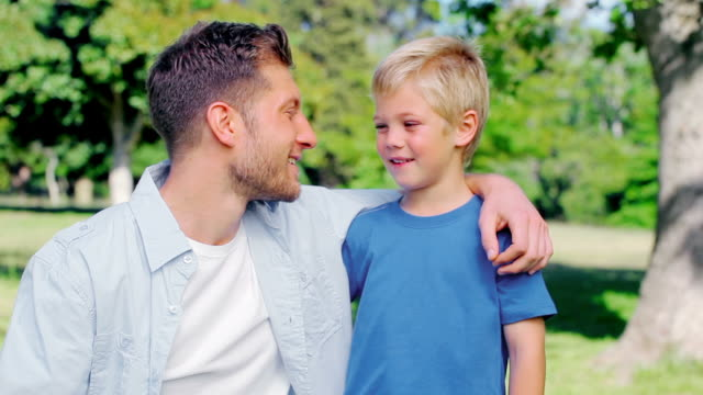 father talking to his son with his arm around his shoulder - alleinerzieher stock-videos und b-roll-filmmaterial