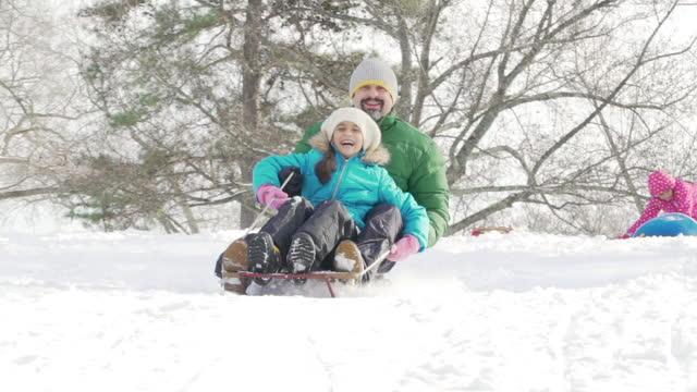 vidéos et rushes de traîneau à neige de père avec des enfants - glisser