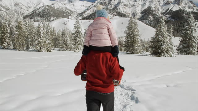 ms pov td tu father snowshoeing away from camera with daughter on shoulders / sun valley, idaho, united states - idaho stock videos & royalty-free footage