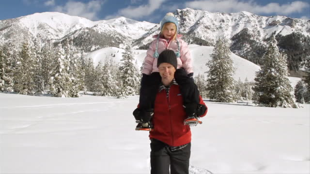 MS POV SLO MO Father snowshoeing toward camera with daughter on shoulders on beautiful winter's day / Sun Valley, Idaho, United States