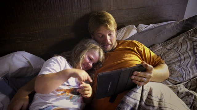 Father snuggles with 8 year old daughter and iPad - Laughter