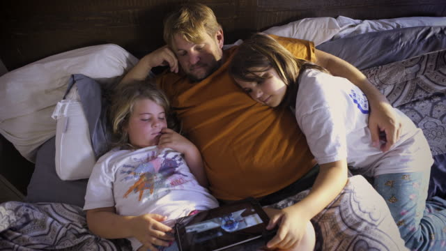 Father snuggles with his two girls and an iPad - sleepy