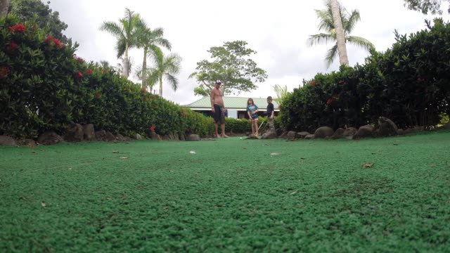father, son and daughter stand in mini golf course and girl takes a shot at the hole and the ball comes towards camera. - kelly mason videos 個影片檔及 b 捲影像