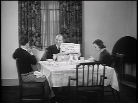 B/W 1935 father, son + daughter sitting at breakfast table / father hands son part of newspaper