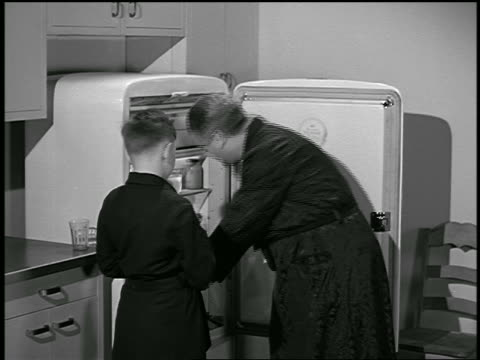 b/w 1946 father + son in bathrobes taking food + milk from refrigerator for snack / industrial - snack stock videos & royalty-free footage