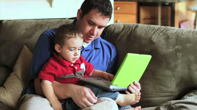 vídeos y material grabado en eventos de stock de padre e hijo computadora portátil - en el regazo