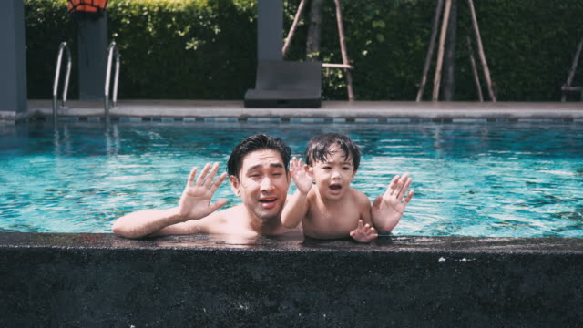 vídeos de stock e filmes b-roll de father & son play in the pool - genderblend