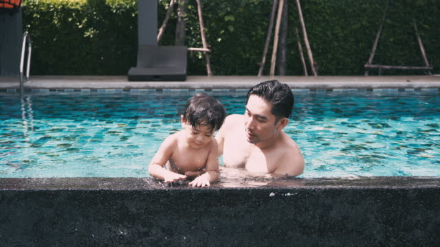 father & son play in the pool - genderblend stock videos & royalty-free footage