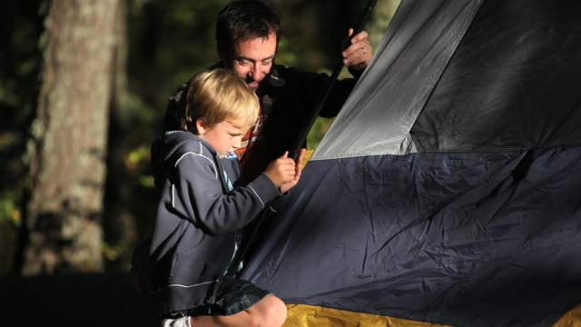 father & son putting up tent - recreational pursuit stock videos & royalty-free footage