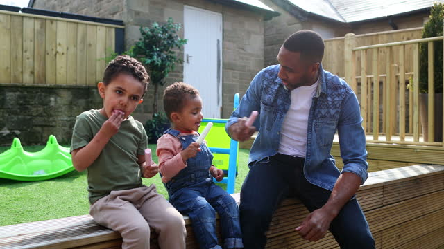 father & sons having ice creams in the garden - genderblend stock videos & royalty-free footage