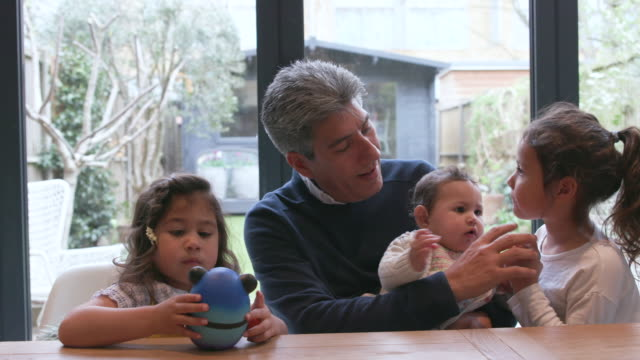 a father spends time at home with his young family - sibling stock videos & royalty-free footage