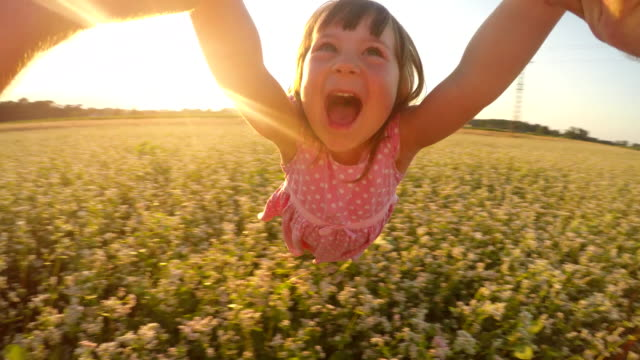 SLO MO POV Father spinning his cute daughter in field