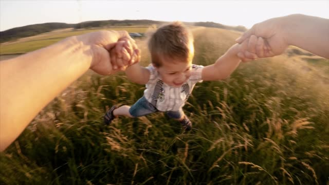 SLO MO POV Father spinning his cute son in grass