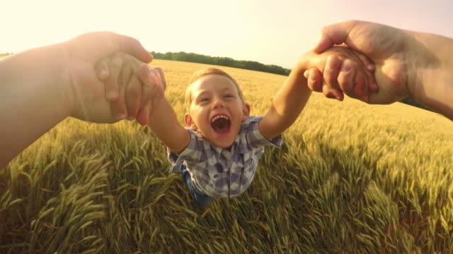 POV 父と彼の息子でスピニングかわいい小麦のフィールド