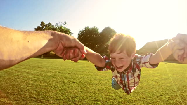 slo mo father spinning his son around - messing about stock videos & royalty-free footage