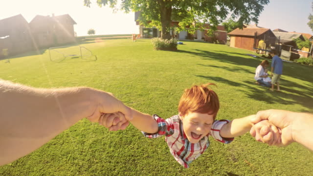 pov father spinning his son around - lawn stock videos & royalty-free footage