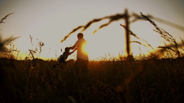 SLO MO Father spinning his son in a meadow