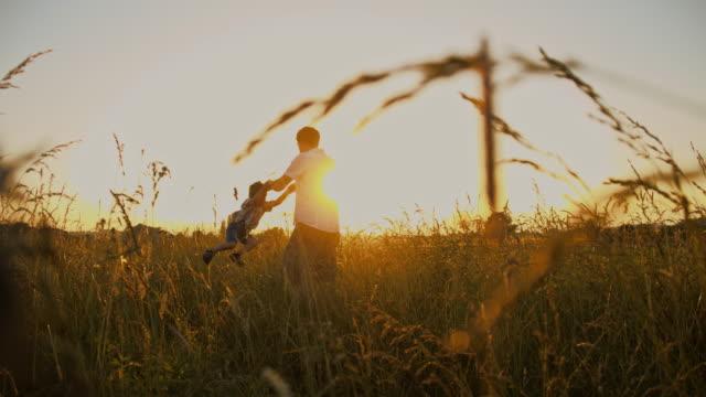 slo mo 父と息子のスピニングの草地 - 息子点の映像素材/bロール