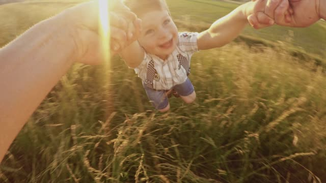 POV Father spinning his son in the meadow